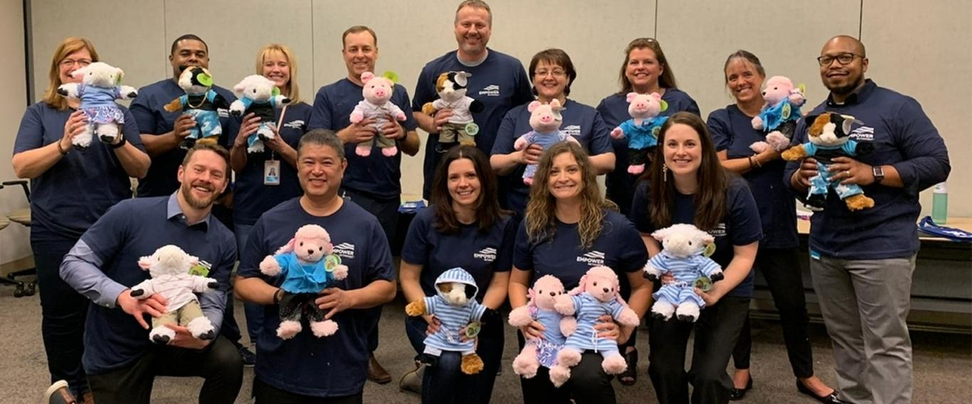 Empower associates display stuffed animals for donation
