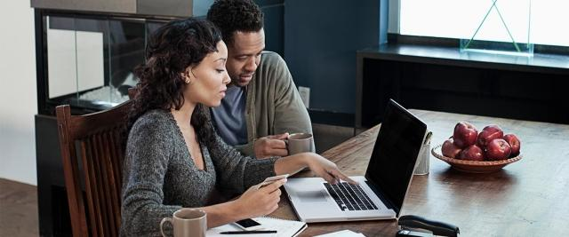 husband and wife sit in front of laptop reviewing finances