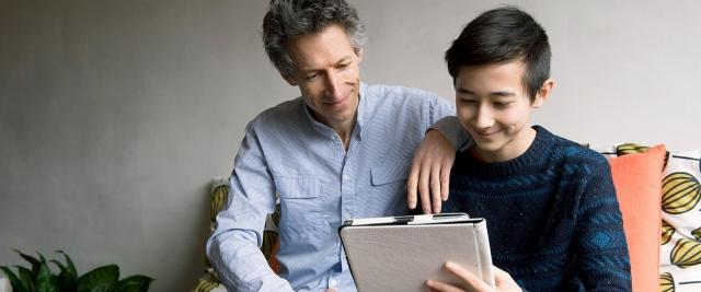 A father sits with son reviewing finances on a tablet device